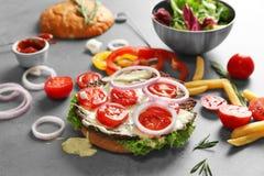 Sammansättning med den smakliga hamburgaren och grönsaker Arkivfoto