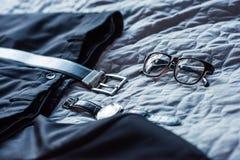 Sammansättning med den svarta klassiska dräkten, bältet, exponeringsglas och armbandsuret fotografering för bildbyråer