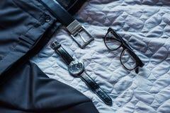 Sammansättning med den svarta klassiska dräkten, bältet, exponeringsglas och armbandsuret royaltyfria bilder
