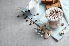 Sammansättning med exponeringsglas av läcker kaffedrink och olika sötsaker på den gråa tabellen arkivbilder