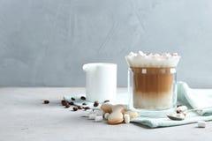 Sammansättning med exponeringsglas av läcker kaffedrink och olika sötsaker på tabellen royaltyfri bild