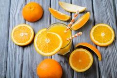 Sammansättning med exponeringsglas av orange fruktsaft och frukter royaltyfria foton