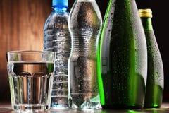 Sammansättning med exponeringsglas och flaskor av mineralvatten Arkivfoto