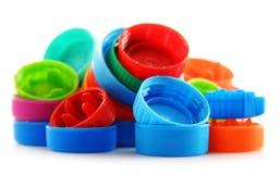 Sammansättning med färgrika plast- kapsyler Arkivfoton