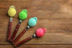 Sammansättning med färgrika skopor av glass i skedar Fotografering för Bildbyråer