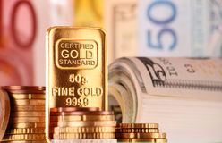 Sammansättning med 50 gram den guld- stången, sedlar och mynt Arkivbilder