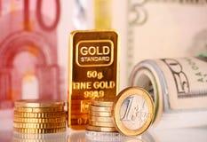 Sammansättning med 50 gram den guld- stången, sedlar och mynt Arkivfoton