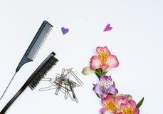 Sammansättning med hårhjälpmedel och blommor royaltyfri fotografi