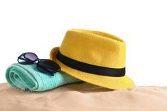 Sammansättning med hatten, strandsand och solglasögon på vit arkivfoto