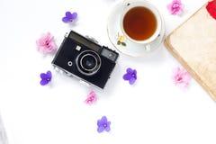 Sammansättning med kopp te, tappningkamera, gamla böcker på bästa sikt för vit bakgrund fotografering för bildbyråer