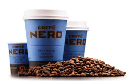 Sammansättning med koppar av Caffe Nero kaffe och bönor royaltyfri foto