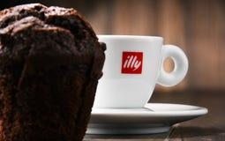 Sammansättning med koppen av den Illy kaffe och muffin Arkivfoto