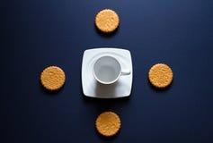 Sammansättning med koppen och kakor på en blå bakgrund Royaltyfria Bilder