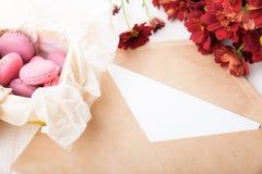Sammansättning med kuvertet, makron och blommor royaltyfri foto