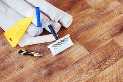 Sammansättning med många rullar av tapeten och olika hjälpmedel för hem- reparation Arkivbilder