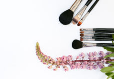 Sammansättning med makeupskönhetsmedel, borstar och blommar på vit bakgrund arkivfoton