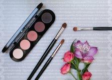 Sammansättning med makeupskönhetsmedel, borstar, shadoes och blommor på grå bakgrund royaltyfria foton
