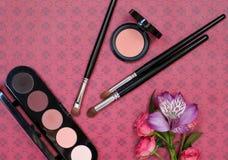 Sammansättning med makeupskönhetsmedel, borstar, shadoes och blommor på röd bakgrund royaltyfri foto