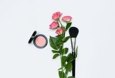 Sammansättning med makeupskönhetsmedel, borstar, shadoes och blommor på vit bakgrund royaltyfria bilder