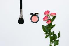 Sammansättning med makeupskönhetsmedel, borstar, shadoes och blommor på vit bakgrund royaltyfri fotografi