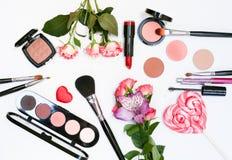 Sammansättning med makeupskönhetsmedel, borstar, shadoes och blommor på vit bakgrund royaltyfria foton
