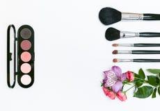 Sammansättning med makeupskönhetsmedel, borstar, shadoes och blommor på vit bakgrund royaltyfri bild