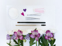 Sammansättning med makeupskönhetsmedel och blommor arkivfoton