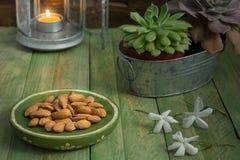 Sammansättning med mandlar, lyktan och blommor royaltyfri bild