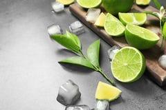 Sammansättning med nya mogna limefrukter och iskuber Royaltyfria Bilder