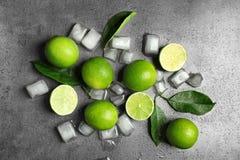 Sammansättning med nya mogna limefrukter och iskuber Fotografering för Bildbyråer