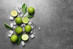Sammansättning med nya mogna limefrukter och iskuber Royaltyfri Foto