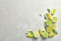 Sammansättning med nya mogna limefrukter på ljus bakgrund Fotografering för Bildbyråer