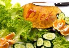 Sammansättning med nya organiska grönsaker och frukter och skärbrädan med inskriften bantar arkivfoton