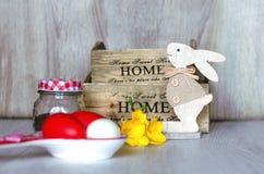 Sammansättning med påskägg, det kokta ägget, den gula blomman och träkaninen, Royaltyfria Bilder