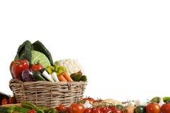 Sammansättning med rå grönsaker i vide- korg Fotografering för Bildbyråer