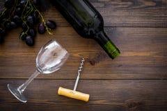 Sammansättning med vin Rött vinflaska, grupp av druvor, korkskruv, vinexponeringsglas på mörk träkopia för bästa sikt för bakgrun fotografering för bildbyråer