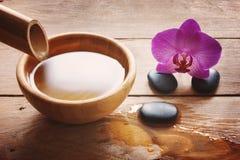 Sammansättning på en trätabell med en bambustam och en bunke av vatten, stenar för brunnsorttillvägagångssätt och en ljus orkidé  royaltyfri fotografi