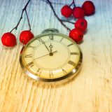 Sammansättning retro klocka för rött bär på en vit trätabell Royaltyfria Bilder