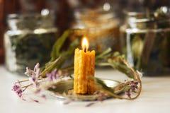Sammansättningen av den brinnande vaxstearinljuset och det torkade riset och blommorna royaltyfri fotografi