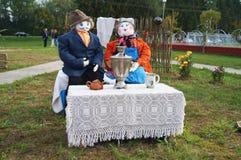 Sammansättningen av dockorna Man och kvinna som dricker te från en samovar i natur Ryssland Royaltyfria Foton