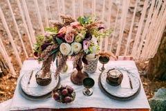 Sammansättningen av olika blommor som står på den tjänade som tabellen i området av brölloppartiet Blom- ordning royaltyfri fotografi