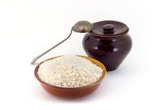Sammansättningen av risgryn i en lera som är pial bredvid en lerakruka och en kopparsked, Royaltyfria Bilder