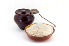 Sammansättningen av risgryn i en lera som är pial bredvid en lerakruka och en kopparsked, Arkivbild
