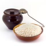 Sammansättningen av risgryn i en lera som är pial bredvid en lerakruka och en kopparsked, Royaltyfria Foton