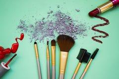 Sammansättningen från en uppsättning av makeup på en turkosbakgrund med skuggor och spikar polermedel Royaltyfria Bilder