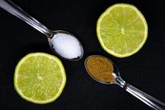 Sammansättningen med två skedar med brunt och vitt socker och med skivorna av limefrukt arkivbilder