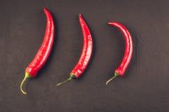 Sammans?ttning av chilipeppar/gl?dhet Chile peppar p? en m?rkerstenbakgrund Top besk?dar fotografering för bildbyråer