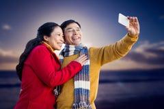 Sammansatt bild av äldre asiatiska par på balkongen som tar selfie Fotografering för Bildbyråer
