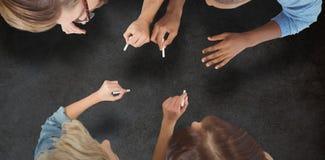 Sammansatt bild av affärsfolk som skriver med chalks arkivfoto