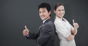 Sammansatt bild av affärsfolk som står baksida mot baksida med tummen upp arkivbild
